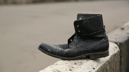 footgear : Old black shoe near the road. Boot near the highway, traffic violation and road accident. Do not run across road