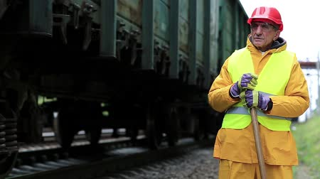 railwayman : Railway man in red hard hat stands near railway tracks and looks at freight train. Railway worker in yellow uniform with shovel in hands. Workman with shovel on railway track Stock Footage