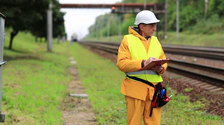 railwayman : Railway worker in uniform with documents. Inspector of railway traffic. Railwayman in yellow uniform on railway line. Inspector of railway traffic makes notes in her documents