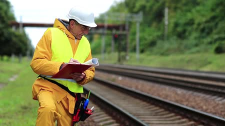 railwayman : Inspector of railway traffic. Railway employee in yellow uniform on railway line. Railway worker in yellow uniform and white hard hat with documents in hands Stock Footage