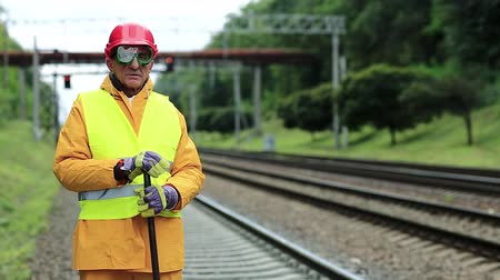 railwayman : Railway worker in uniform. Railway man in red hard hat stands on railway tracks and looks at the camera. Workman with metal crowbar on railway track Stock Footage