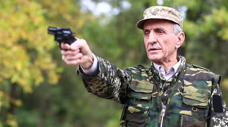 harcias : Senior man in military uniform shoots a revolver. Man with black gun. Senior man in military uniform shoots a revolver. Retired officer at shooting range. Senior man shoots a pistol in forest