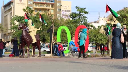 mussulman : JORDAN, AQABA, DECEMBER 16, 2016: People near the monument to the centennial of the Great Arab Revolt, Ayla Square in Aqaba, Jordan, officially The Hashemite Kingdom of Jordan