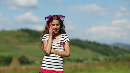 babbler : Pretty girl stands on the meadow and speaks on cell phone. Attractive girl with big glasses on the head in the shape of stars stands on a grassland and speaks on a smartphone. Female with smartphone Stock Footage