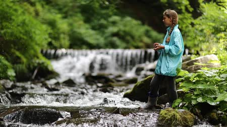 hurl : Girl throws in a small river. Girl in blue jacket stands near small overflow dam on the river in the forest
