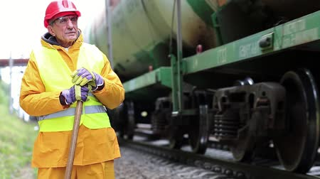 slogger : Railway man in red hard hat stands near railway tracks and looks at freight train. Railway worker in yellow uniform with shovel in hands. Workman with shovel on railway track Stock Footage