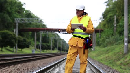 railwayman : Railway worker in yellow uniform. Railway worker makes notes in his tablet computer. Railway worker in yellow uniform on railway line