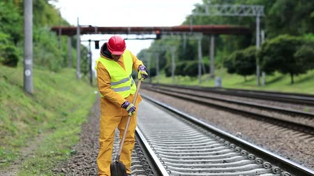 railwayman : Repairman worker in yellow uniform with shovel in hands mends railway line. Railwayman in yellow uniform with shovel in hands. Workman with shovel on railway track