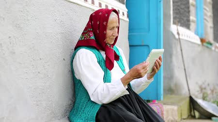babbler : Old woman sits on bench and communicates via tablet computer. Senior woman sits on a bench. Ukrainian old woman with tablet pc communicates through skype