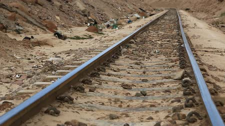 aqaba : Trash lies near decauville. Rubbish near light railway. Garbage lies near narrow gauge railway in Aqaba, Jordan