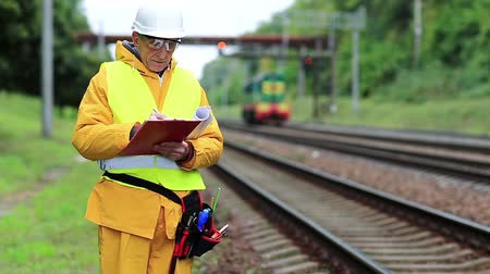 railwayman : Railway worker in uniform with documents. Inspector of railway traffic. Railway employee in yellow uniform on railway line. Inspector of railway traffic makes notes in her documents
