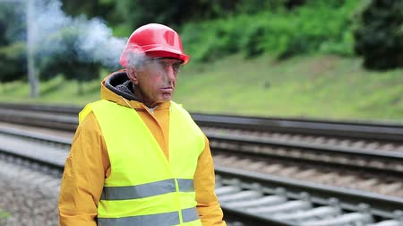 slogger : Railway man in red hard hat stands on railway track and smokes. Working man with cigarette on railway tracks. Smoke break. Railway worker in yellow uniform stands on railway line