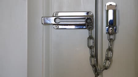 защелка : Womans movements safety chain to open the door. Womans hand and door safety chain Стоковые видеозаписи