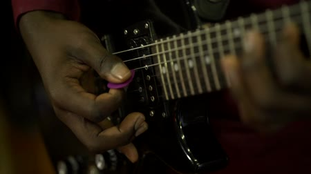 serenade : Acoustic six-string guitar. The black man plays the guitar. Club lighting. Very large plan. Macro shooting.