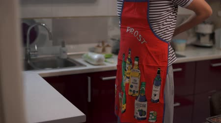 A man wearing an apron to cook food. Dress and tie a red kitchen apron. Wants to make a wife a surprise.
