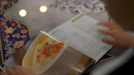 The boy flips through the pages of a book with culinary recipes. A father and his sons want to make a mom a surprise. Stok Video