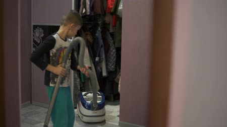 The boy takes a vacuum cleaner to clean the room. Helps parents on home affairs. Stok Video