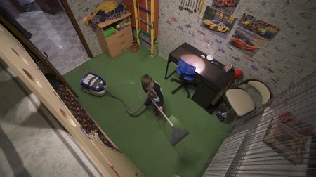 The boy is vacuuming in the room. Helps parents on home affairs. Top view.