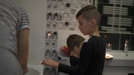 Dad with two sons prepare a surprise for mom. They light candles in the bathroom and sprinkle with petals of roses.