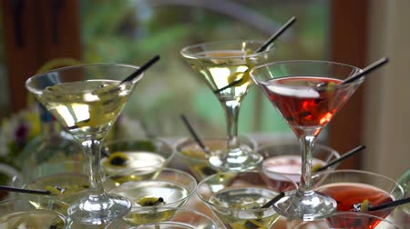 Alcoholic Paradise. The glasses filled with martini are on the table. In the glasses the wine is red and yellow. Stated in a chess game. Slow motion