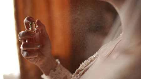 perfume bottle : The bride gently spray perfume around his neck. The video is slower. Still shot in the backlight. Slow motion Stock Footage