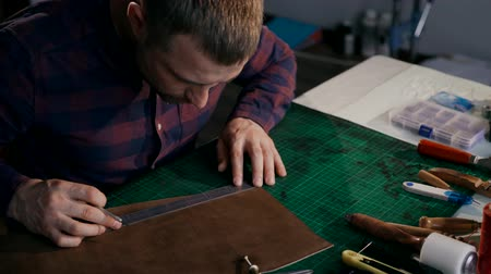 собственность : The process of manufacturing a leather wallet handmade. The wizard makes a mark on the leather bark. Own business. Handmade.