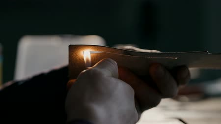 собственность : The process of manufacturing a leather wallet handmade. The artisan handles a piece of leather with a fire. Handmade leather goods. Macro.
