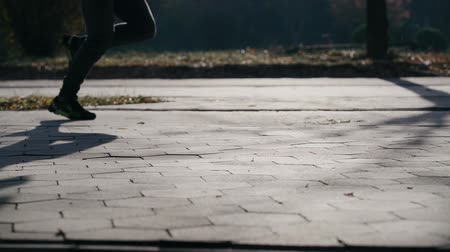 кроссовки : The offset runs in the frame from left to right, reflecting the shadow on the track. Only the athletes legs are visible in the frame. Slow motion