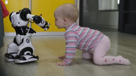 The little girl carefully looks at the toy robot and dances with him. Modern Robotic Technologies Stok Video