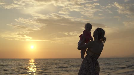Mother holds a small daughter in the background of the sunset. The seaside of Italy.