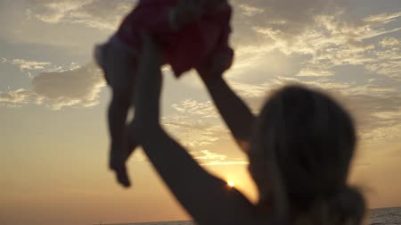 Mother throws a small daughter on the back of the sunset on her hands. The seaside of Italy. Stok Video