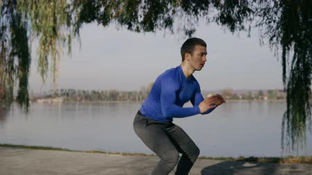 Athlete performs physical exercises on the shore of the lake.