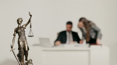 Statue of Justice on the background of two people who work with documents.