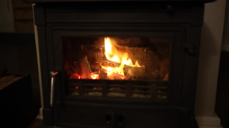 wood burner : footage of an indoor warming house fire burning brightly as logs turn to embers in the flames
