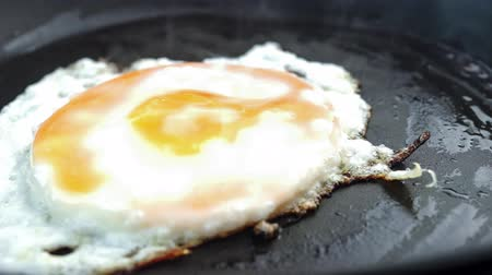 cozinhado : Closeup of greasy fried egg on frying pan with cooking audio