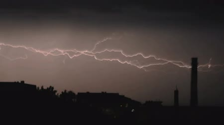 гром : Slow motion video clip of lightning and severe thunderstorm clouds above the city at night.
