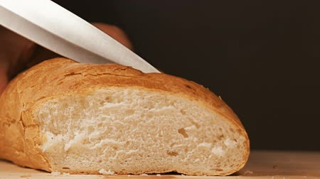 piekarz : Baker is cutting slice of his freshly baked bread with kitchen knife on a wooden surface