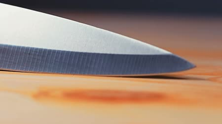 garfos : Blade of the knife tilts on a wooden background and the light is shines on the surface