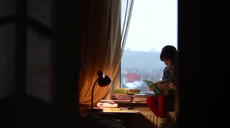 drawer : Young girl read the book near rainy window