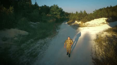 определенный : Certain military man walking across sandy road