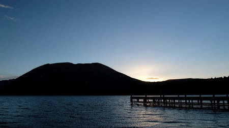 The sunset scene at lake, Silhouette wooden silhouette Jetty mountain view. Seamless 4K Video