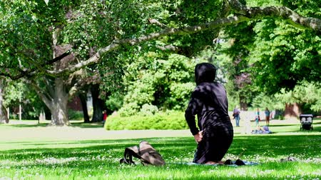 A man wears a black hoodie doing yoga on the grass under the trees in the park. Clam and peaceful scene. 4K Video. Stock mozgókép