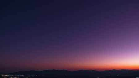 starry sky : Day to Night Timelapse, Beautiful orange and violet sunset dusk scene above the high mountain turning to the night scene with many stars. 4K Video.