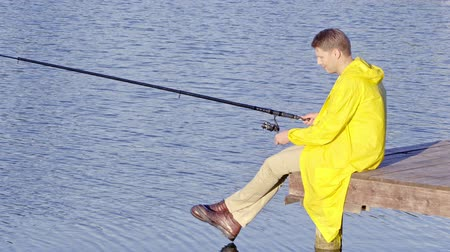 raincoat : Young man fishing outdoors