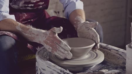 clay pot : Young potter in uniform in workshop