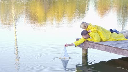 raincoat : Family with a wooden ship Stock Footage