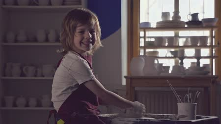 глина : Little child in a pottery Стоковые видеозаписи