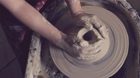 clay pot : Childrens hands are molded on a potters wheel Stock Footage