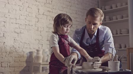 clay pot : Father and son in a pottery workshop Stock Footage
