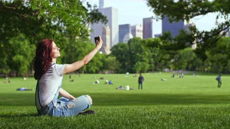 york : Young girl doing selfie in Central Park Stock Footage